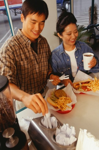 Couple receiving order in fast food restaurant : Stock Photo