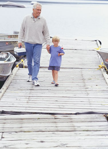 Grandfather and grandson (6-7) walking on pier : Stock Photo