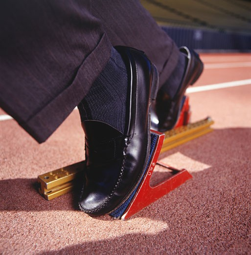 Businessman with feet in starting blocks, close-up, low section : Stock Photo