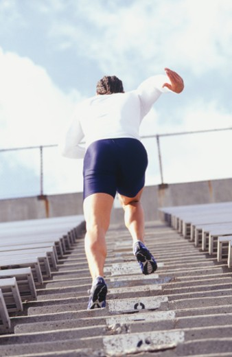 Stock Photo: 1598R-138857 Man running up steps at sports stadium, rear view, low angle view