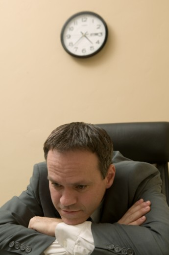 Tired businessman sitting and leaning on desk in office : Stock Photo