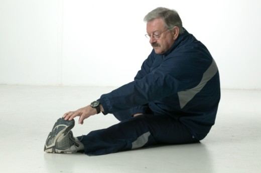 Man with moustache, sitting performing stretching exercises, posing in studio, portrait : Stock Photo