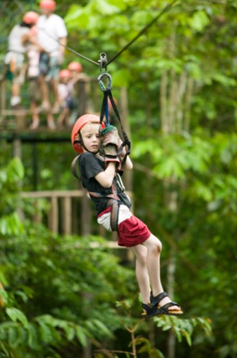 Girl (6-7) in helmet going down on rope : Stock Photo