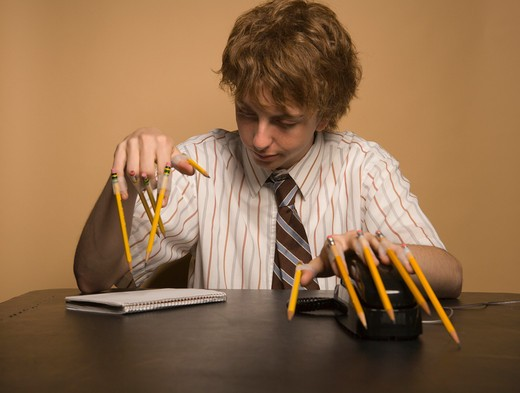 Young man with pencils taped on fingers : Stock Photo