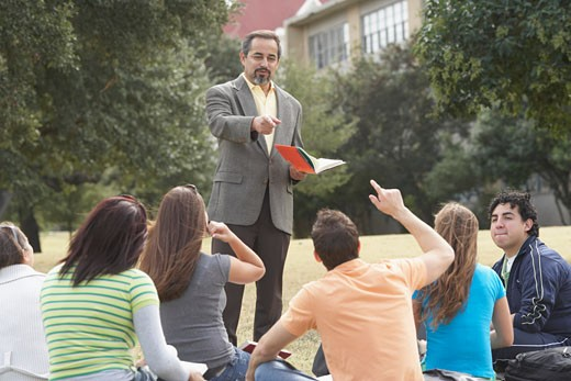 Male lecturer teaching  students on a lawn : Stock Photo