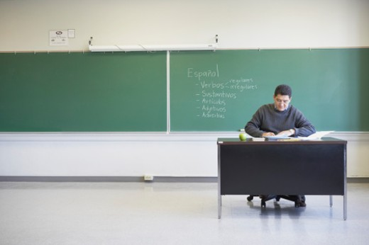 Stock Photo: 1598R-140288 Male lecturer sitting at a desk in a classroom