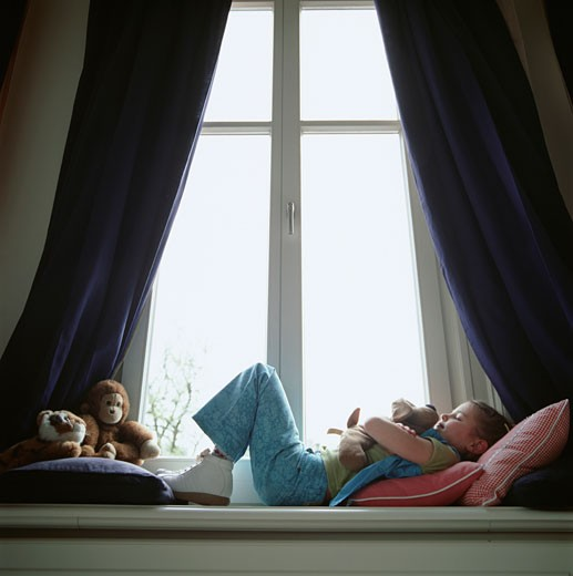 Girl (6-7) lying on window sill, hugging toy dog : Stock Photo