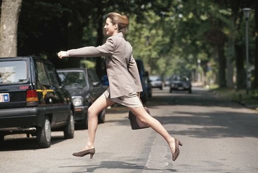 Businesswoman running across road, side view : Stock Photo