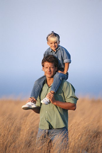 Stock Photo: 1598R-141315 Father holding daughter (6-7) on shoulders in field, smiling
