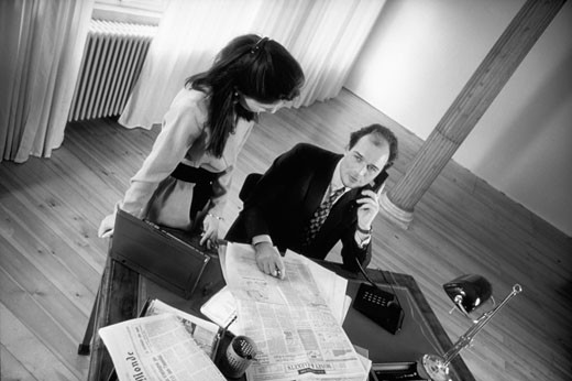 Businessman and woman at office desk, man on phone, elevated view (B&W) : Stock Photo