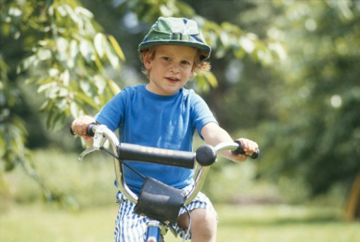 Stock Photo: 1598R-141568 Boy (6-7) riding bicycle, smiling
