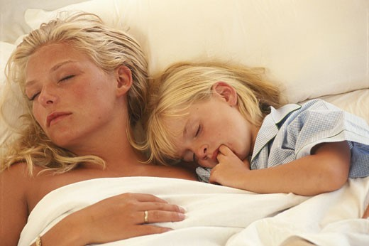 Mother with daughter (6-7) sleeping on bed, elevated view : Stock Photo