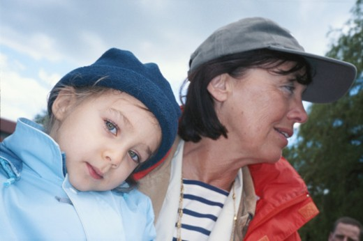 Girl (3-5) leaning on grandmother, outdoors : Stock Photo