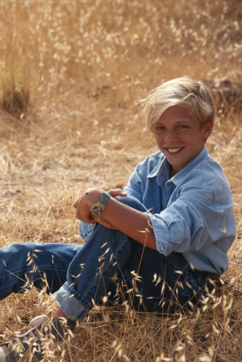 Boy (10-11) sitting in field, smiling, portrait : Stock Photo