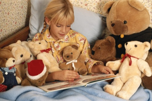 Girl (6-7) sitting on bed reading book with soft toys : Stock Photo