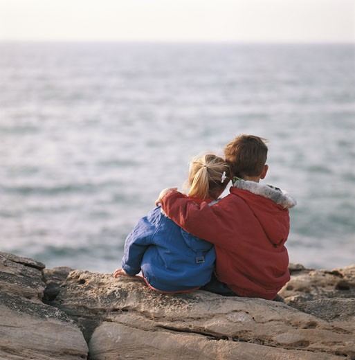Stock Photo: 1598R-142119 Girl and boy (4-7) sitting on rock by sea, rear view