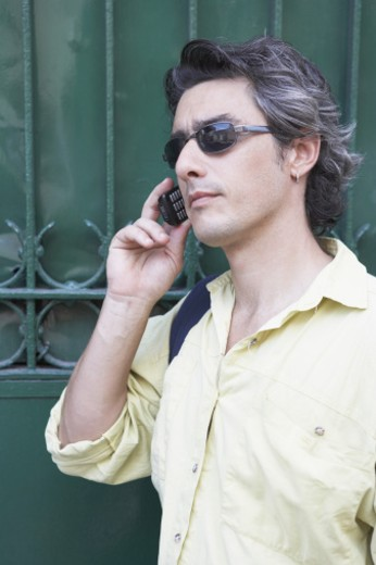 Stock Photo: 1598R-142221 Side profile of a mid adult man talking on a mobile phone