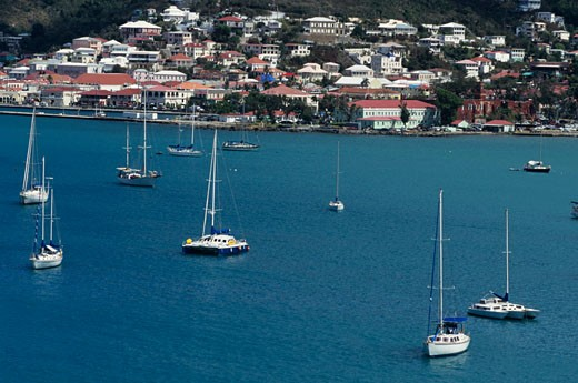 Sailing boats anchored in bay, town in background, aerial view : Stock Photo