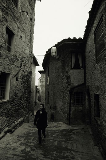 Stock Photo: 1598R-143052 Woman walking up stone steps between old buildings, San Gimignano, Italy, (B&W)