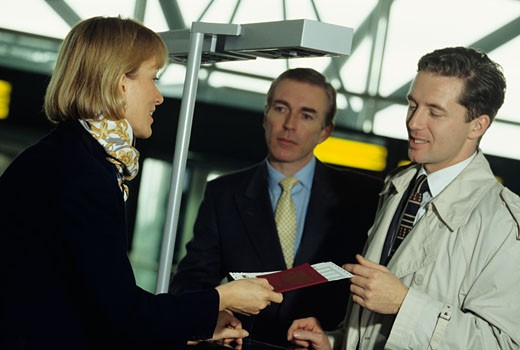 Businessmen at airport check-in desk with female airline employee : Stock Photo