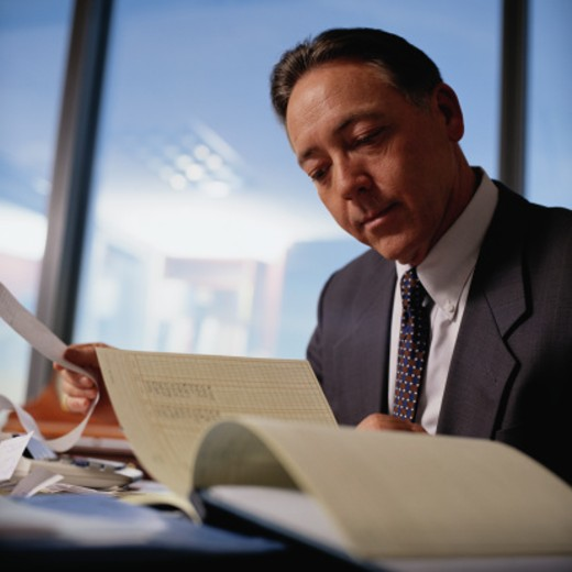 Businessman Looking Over a Ledger : Stock Photo