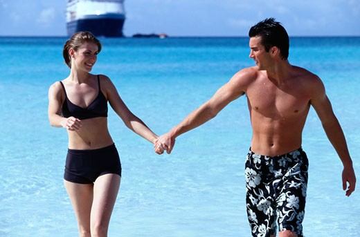 Stock Photo: 1598R-147396 Young Couple Holding Hands in the Sea