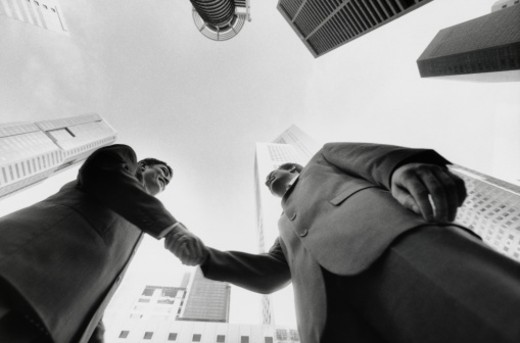Stock Photo: 1598R-148450 Two Businessmen Shaking Hands Amid Skyscrapers