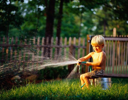 Boy Watering the Lawn : Stock Photo