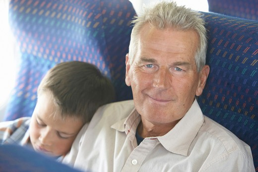 Boy (9-11) sleeping on grandfather's shoulder on airplane : Stock Photo