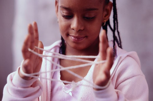 Girl Playing Cat's Cradle : Stock Photo