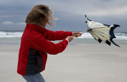 Woman holding umbrella on beach, struggling against wind : Stock Photo