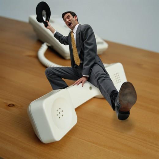 Businessman Cowboy Riding Telephone Receiver : Stock Photo