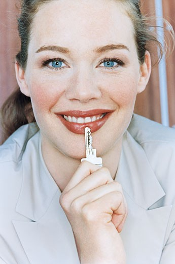 Woman resting key on lip, smiling, portrait : Stock Photo