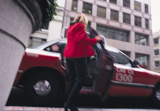 A blonde businesswoman dressed in a red blazer and black pants gets into a red cab in front of a white building : Stock Photo