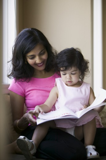Stock Photo: 1598R-161585 lifestyle shot of a mother as she reads to her toddler daughter that sits on her lap