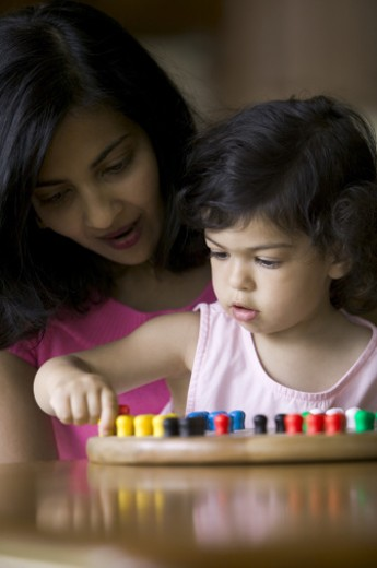 lifestyle shot of a mother as she sits and helps play a game with her toddler daughter : Stock Photo
