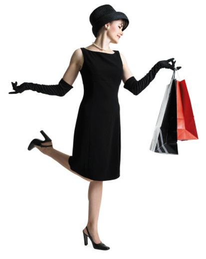 ilhouette sophisticated woman in black dress hat as she holds shopping bags and kicks up her foot : Stock Photo