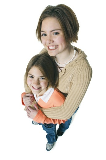 a caucasian teenage female smiles as she embraces her little sister from behind : Stock Photo