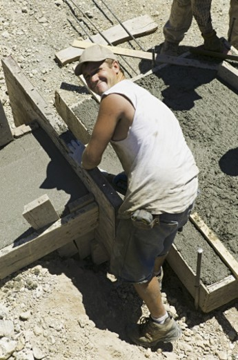 lifestyle shot of an adult male construction worker in work clothes as he lays cement : Stock Photo