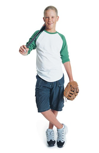 a young caucasian boy is wearing blue shorts and a t-shirt as he stands crosslegged with a baseball bat over his shoulder and has a baseball glove on his hand : Stock Photo