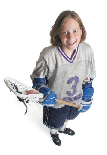 a teenage caucasian female in a white jersey holds her lacrosse racket and smiles as she looks up into the camera : Stock Photo