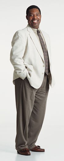 handsome middle aged african american man dressed in a light blazer and brown pants looking into the camera with his hands in his pockets : Stock Photo