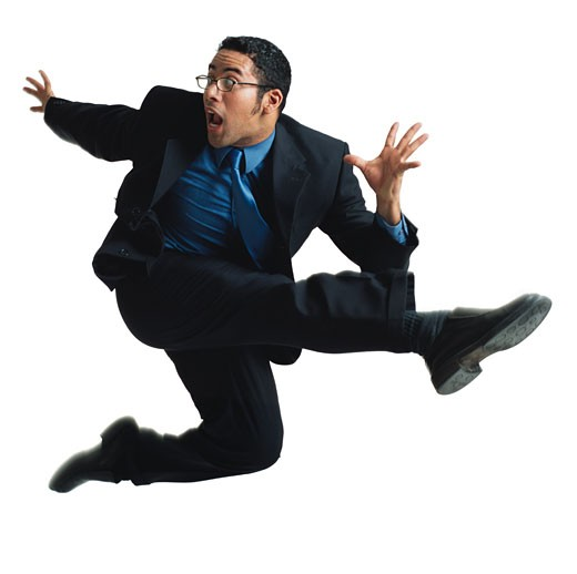 a young latin male dancer with glasses in a black business suit and blue shirt and tie jumps up and kicks wildly in the air while looking surprised : Stock Photo