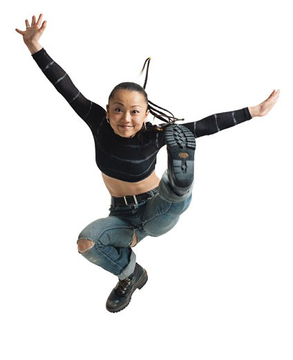 young asian female ripped jeans and blue shirt braid hair jumps into the air and flairs arms smiling : Stock Photo