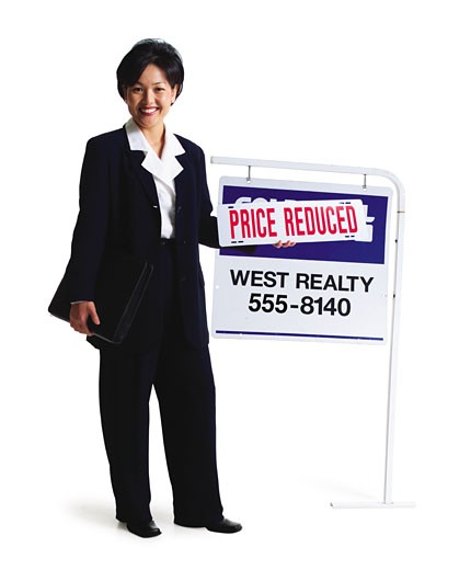 an asian female realator stands smiling by a for sale sign : Stock Photo