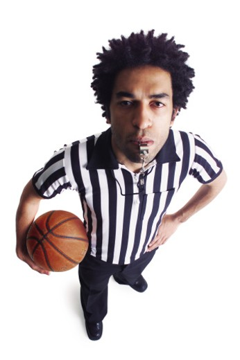 an african american male referee blows his whistle as he looks up at the camera : Stock Photo