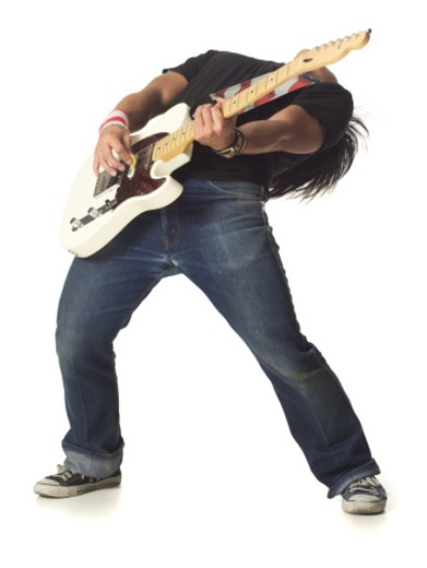 an asian male teen in jeans and a black shirt leans back while playing an electric guitar : Stock Photo
