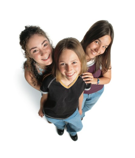 three teenage caucasian girls smile up at the camera playfully : Stock Photo
