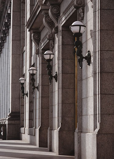 lamps along the pillars of a stone building stand in a line with each other : Stock Photo