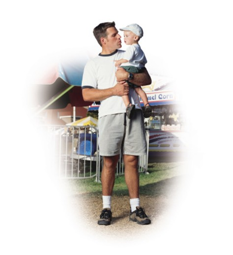 a young caucasian father in gray shorts and a white t-shirt is at a fair holding his baby son who is wearing a white baseball cap : Stock Photo